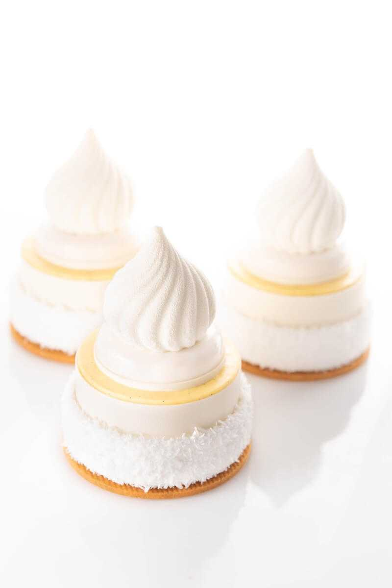 miniature white cakes with intricate top decoration