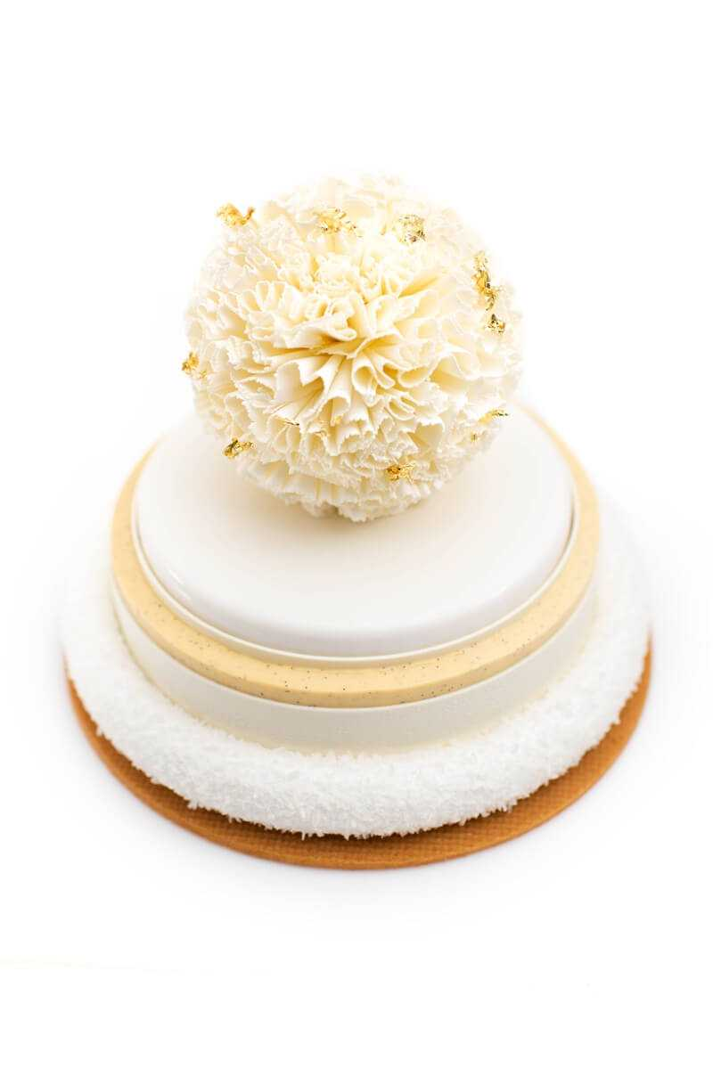 white cake with intricate top decoration