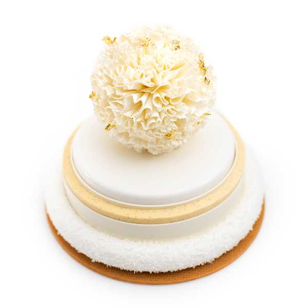 a small white cake with gold flakes on top